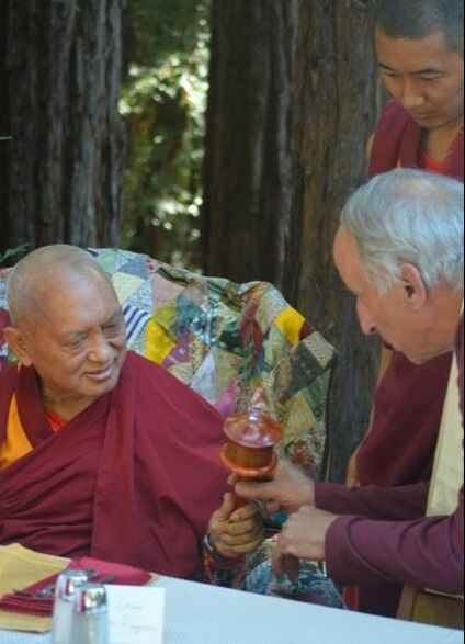 Chuck offering a handheld prayer wheel to Lama Zopa Rinpoche at Vajrapani Institute